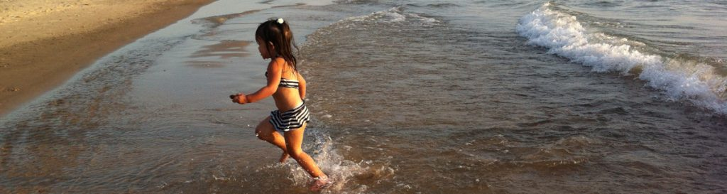 child-running-at-waters-edge