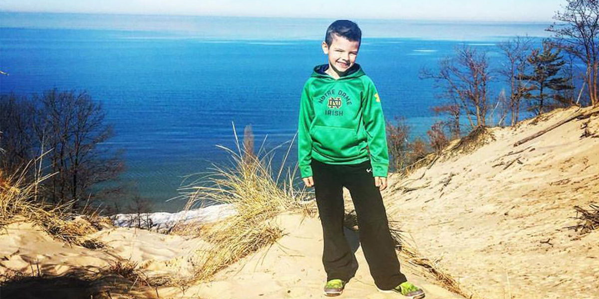 Noah Albert atop a sand dune on the shores of Lake Michigan