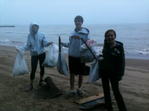 Three of Tor Solberg's five children cleaning up Maple St. Beach in Winnetka, Illinois.