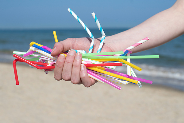 Hand holding straws on a beach