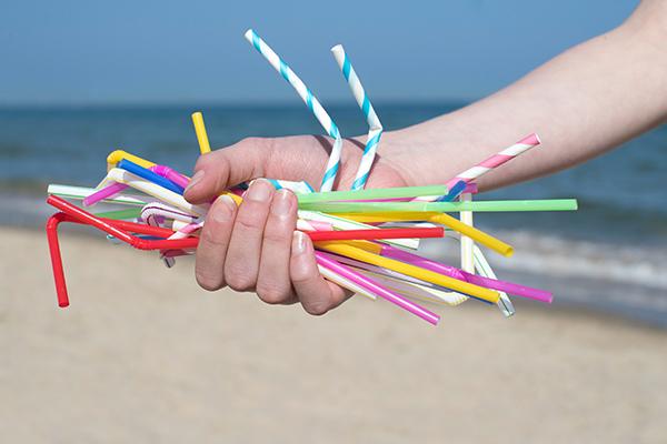Hand holding straws on a beach