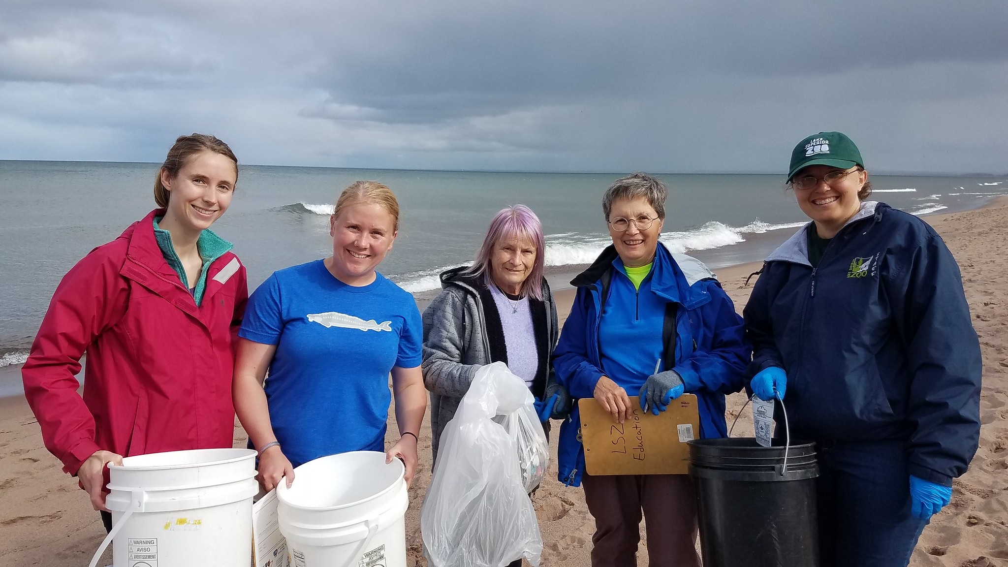 Five women at Adopt-a-beach holding trash and buckets