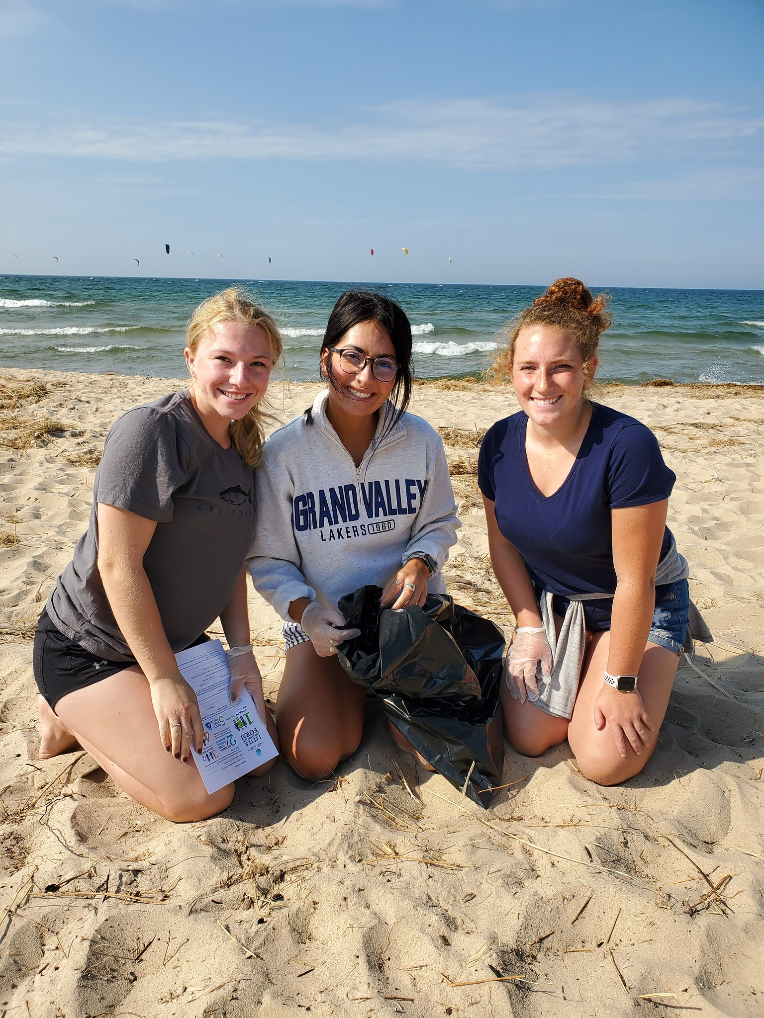 Three volunteers in sand in front of water