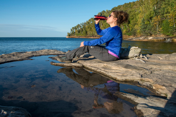 Women drinking from a water bottle on a Lake Superior shore, photo by Lloyd DeGrane